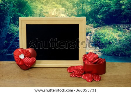 heart and blackboard with waterfall and forest background - stock photo