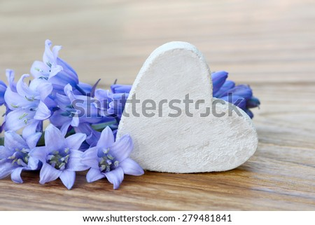 Heart and blue flowers lying on wood - stock photo