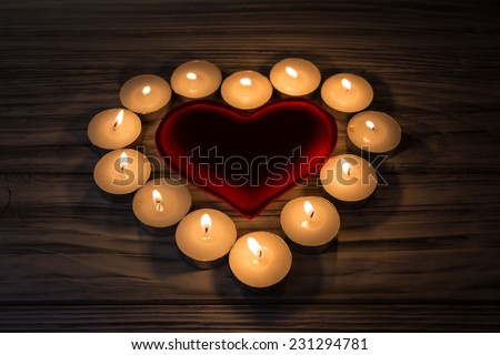 Heart and candles on a wooden background - stock photo