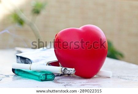 heart and care concept: cigarette and heart shape on the table. - stock photo