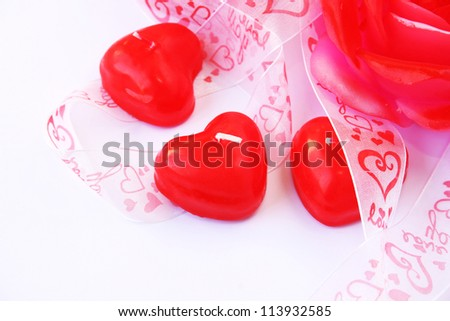 Heart and rose shape red candles  and ribbon on grey background.