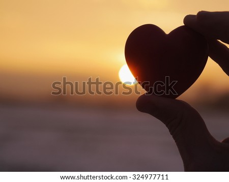 Heart at sunset out doors - stock photo