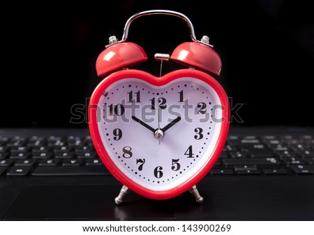 heart clock on a laptop - stock photo