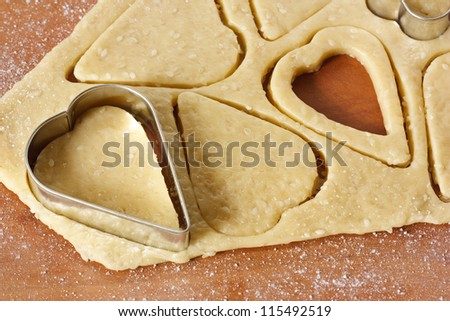 Heart cookies cutter on raw cookie dough.