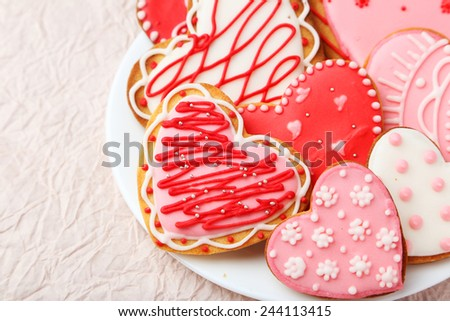 Heart cookies on white plate on pink paper background - stock photo