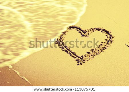 heart drawing in the sand beach - stock photo