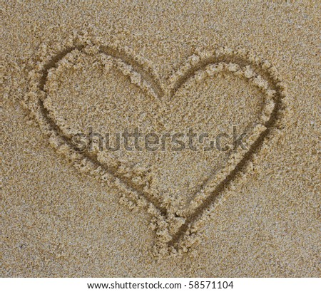 Heart drawing in the sand on the beach - stock photo