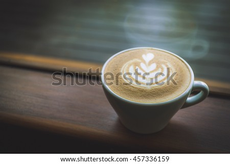 heart drawing on latte art coffee cup on a side of the window in the morning, selective focus, vintage photo and film style - stock photo