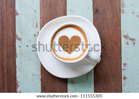 heart drawing on latte art coffee , wood color background - stock photo