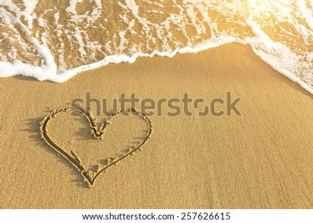 Heart drawn in sea beach sand, soft wave in a Sunny summer day. - stock photo