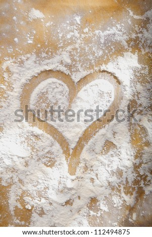 Heart drawn in sprinkled cooking flour symbolic of a love and enjoyment of baking or as a romantic symbol of love for an anniversary or Valentines - stock photo