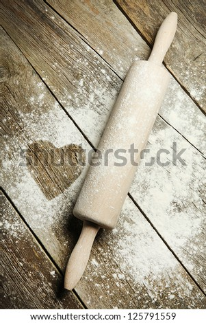 Heart drawn in sprinkled cooking flour. Wooden rolling pin with remnants of flour in a rustic kitchen on an old grainy textured wood surface - stock photo