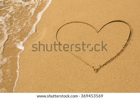Heart drawn on the beach sand with a soft wave. - stock photo