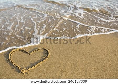 Heart drawn on the sand of a sea beach. - stock photo