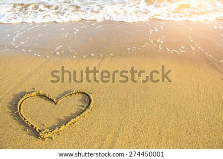 Heart drawn on the sand of ocean beach. - stock photo
