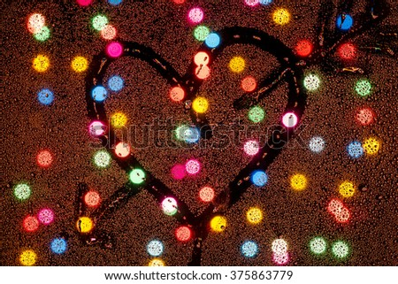 Heart drawn on wet glass amid colorful circle Bokeh - stock photo