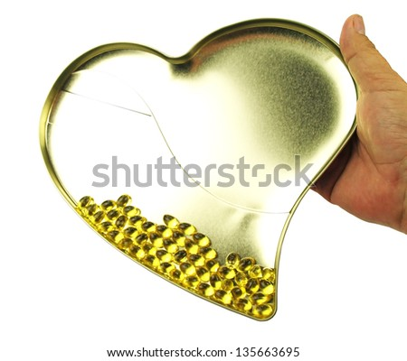 Heart filled with omega 3 in hand - stock photo