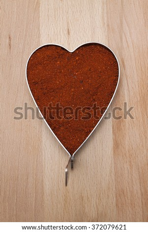 Heart filled with red pepper, chili flakes - stock photo