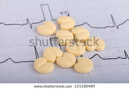 Heart form pills over an electrocardiogram graph - stock photo