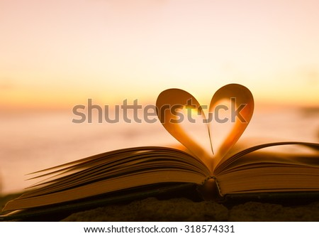 Heart from a book page against a beautiful sunset.  - stock photo
