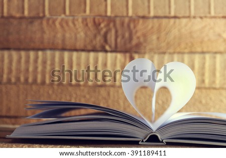 Heart from book pages on wooden blurred background