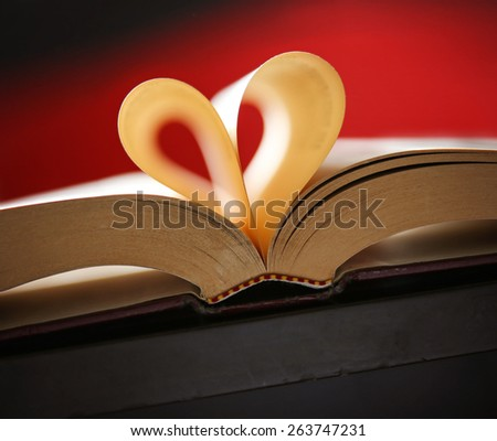 Heart from book pages with a shallow depth of field and a red background  - stock photo
