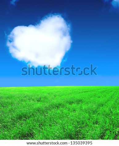 Heart from clouds and green field