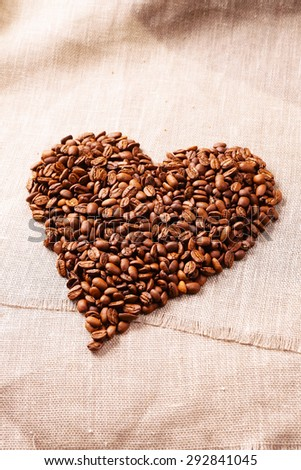 heart from coffee beans on the rough cloth background - stock photo
