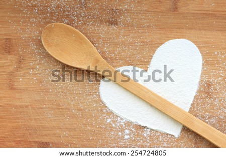 heart from flour on wooden background - stock photo