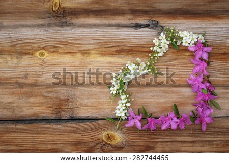 heart from flowers on wooden background