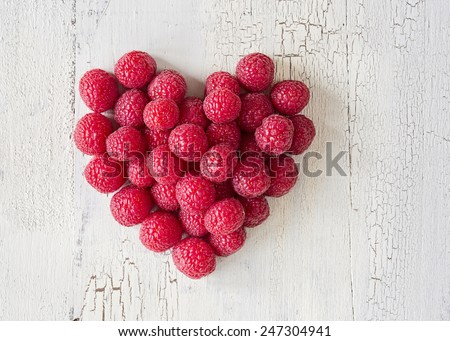 Heart from raspberries on a vintage wooden background - stock photo