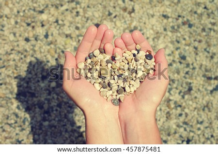 Heart from sea a pebble in female hands. Festive love background