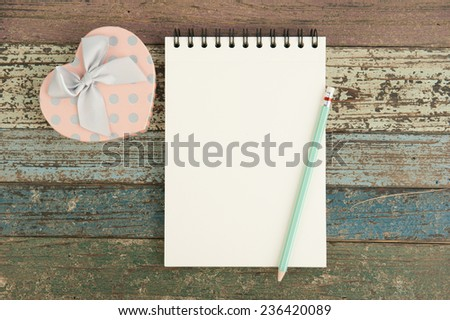 Heart gift box and notebook on vintage wood table for background - stock photo
