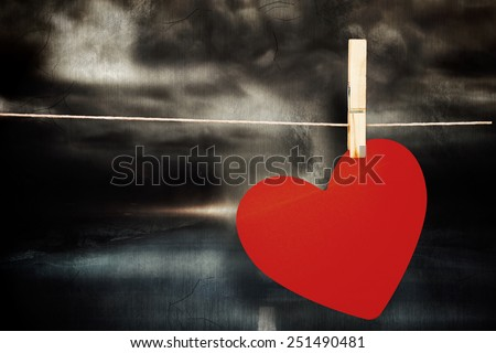 Heart hanging on line against stormy sky with tornado over road - stock photo