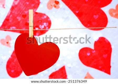 Heart hanging on line against valentines heart design