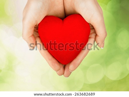 Heart. Health and charity concept - close up of woman hands holding heart - stock photo