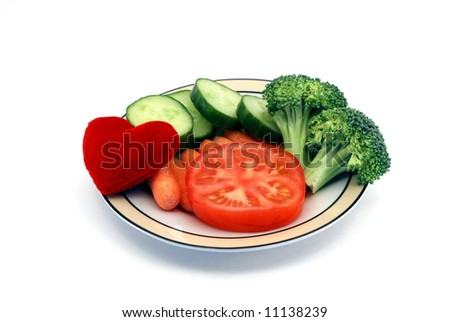 Heart healthy snack concept with a dish of vegetables and plush heart toy isolated on a white background - stock photo