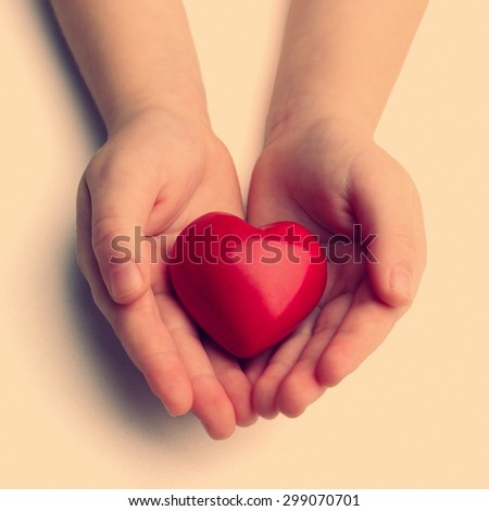 Heart in child hands on light background - stock photo