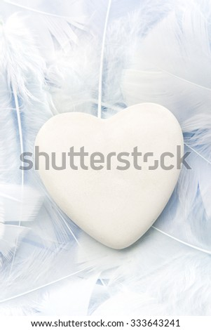 Heart in feathers, valentine or mother's day background. - stock photo