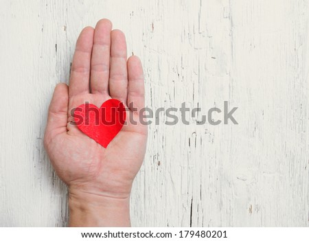 Heart in human hand. White wood background. Retro tinted. - stock photo