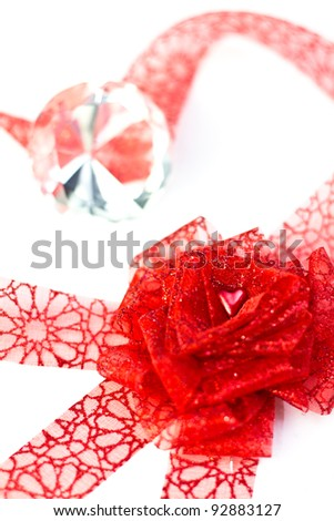 Heart in ribbon forming a rose in front of diamond on white background. Shallow depth of field.