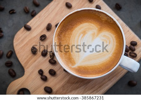 Heart in the coffee cup on the table. - stock photo