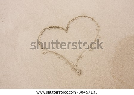 Heart in the sand at the beach - stock photo