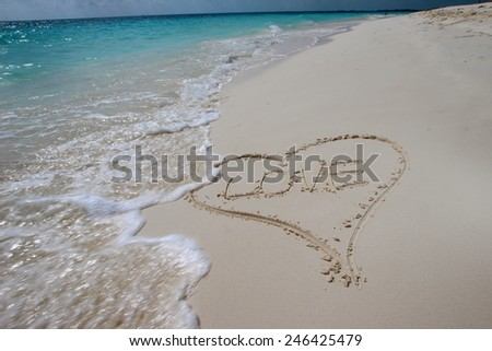Heart in the sand on the beach with the word LOVE - stock photo