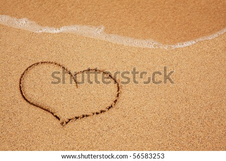 Heart in the sand with wave rolling