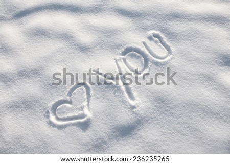 Heart in the snow. Love you word message on the snow.