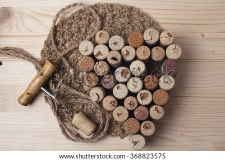 Heart laid out from bottle corks and corkscrew on wooden background - stock photo