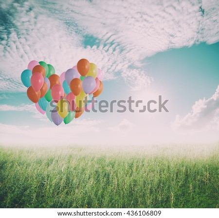 Heart love Color balloons in grass fields and Sun clouds sky for background.Copy Space.Vintage Tone - stock photo