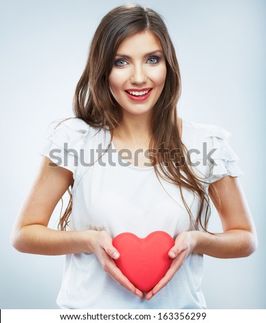 Heart. Love symbol. Portrait of beautiful happy woman hold Valentine day symbol. Isolated studio background female model. Beautiful girl.