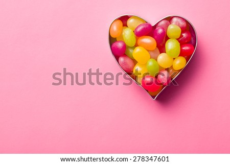 heart made from jelly beans on pink background - stock photo